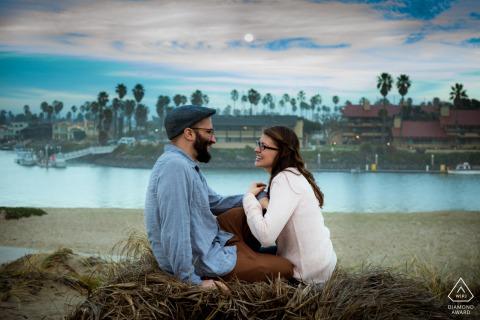 Pareja en la playa en una noche con luna llena en el Marina Park, Ventura, CA