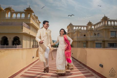 Engagement shoot at the Vijay Runn Palace, Jaipur, India of a couple running during mid-day with two strobes