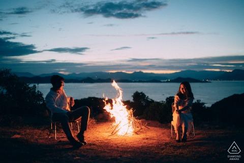 Een verloofd paar zit rond een brand in Binh Ba Island, Cam Ranh, Vietnam