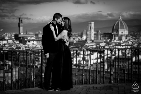 Newly engaged couple is in the terrace at piazzale Michelangelo in Florence