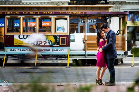 San Franciscoengagement photo session | A hug in front of a passing cable car