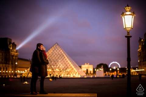 Couple fiancé devant la pyramide du Louvre à Paris, France