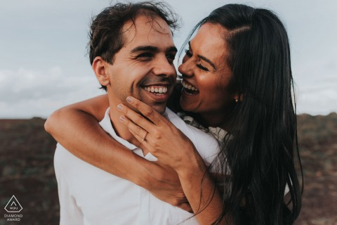 The engaged couple smile and laugh with one another during their Belo Horizonte photo session