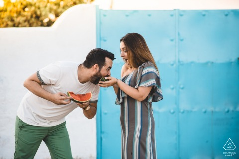 A playful couple playing and eating watermelon in Athens, Greece during an engagement portrait shoot