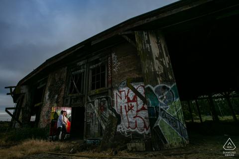 Una pareja comprometida entre grafitti en el patio de trenes Bayshore Roundhouse