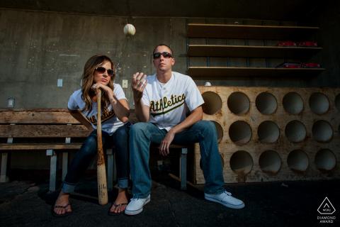 Stockton, California, pareja luciendo su atuendo de béisbol con pelota y bate durante su sesión de fotos de compromiso