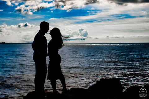 Toronto couple are silhouetted against the sky near the waters edge in Ontario, Canada