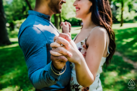 Face to face couple hold hands outstretched for an engagement portrait in Toronto, Ontario