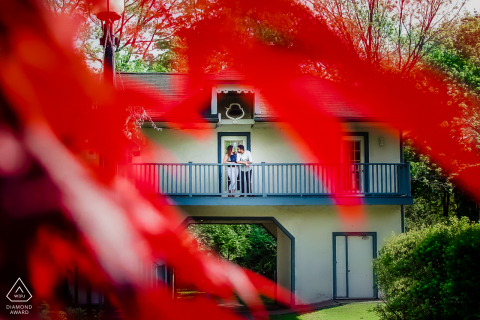 Couple shot through red leaves while they enjoy a moment of time on the balcony in Mississagua, Ontario