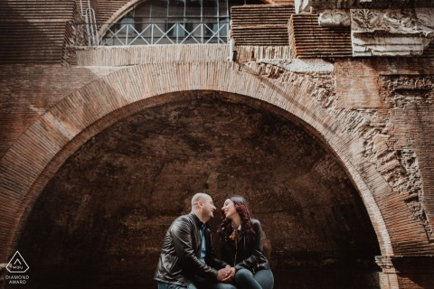 Engagement portrait session of a couple framed within an arch in Rome, Italy