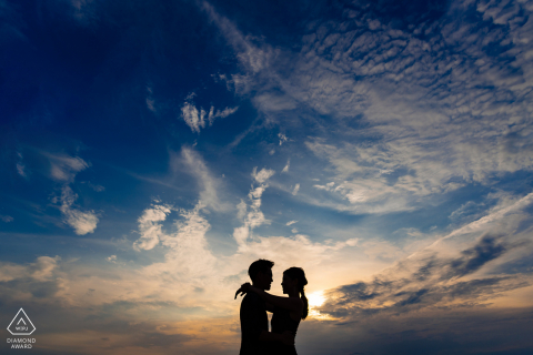 Pre-wedding shooting in Da Nang of couple silhouetted against a sunset sky