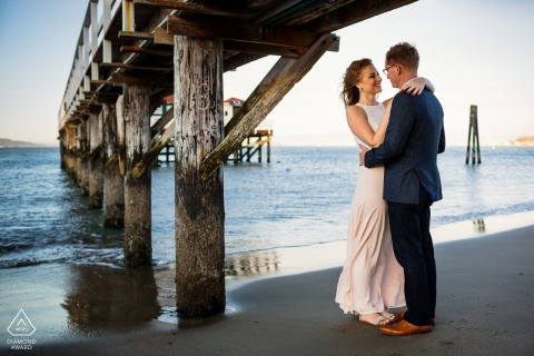 An embrace under the pier during an engagement shoot in San Francisco