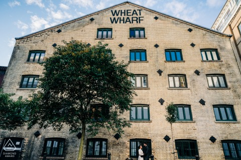 Shad Thames, London, UK |	A couple embrace and framed by large historic building, Wheat Wharf