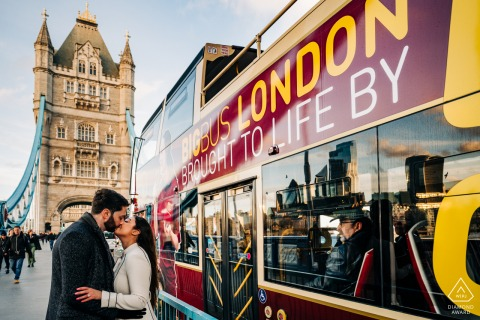 Passenger on passing bus watches couple stopping to kiss on the London Bridge in London, UK