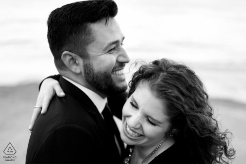 an engaged couple laughing on the beach in black and white in Chicago, IL