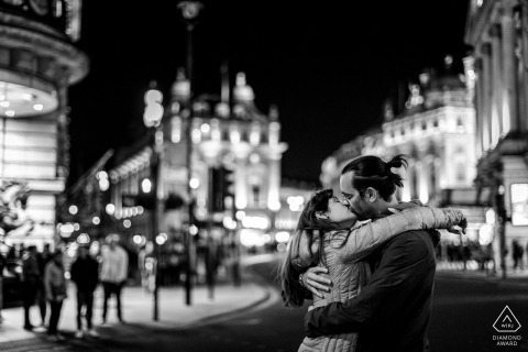 A newly engaged couple kiss at Piccadilly Circus in London, UK