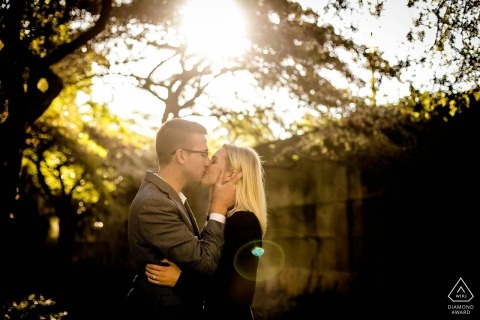 a Chicago Illinois young couple kiss under the sun and trees during portrait shoot