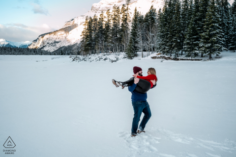 a Lake Minnewanka, AB, Canada Couple is having a good time during the winter engagement session.