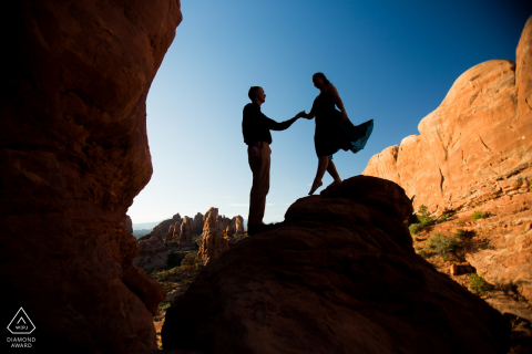 Arches National Park, Utah the groom gives a hand down from a rock in Moab during their sunrise desert engagement session