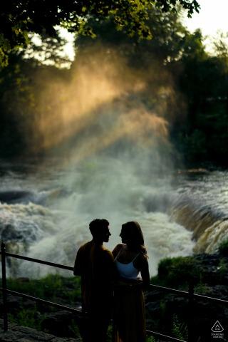 Séance photo avant le mariage de Passaic Falls avec un couple debout près de la chute d'eau