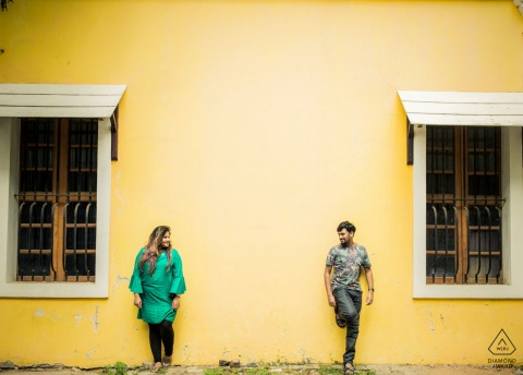 Pudhucherry, India couple Exchanging love against a blank yellow wall during portrait session