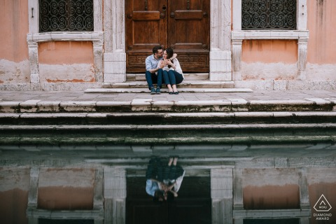 Venice (Italy) Engagement session with a couple sitting on the steps with their reflection on the water