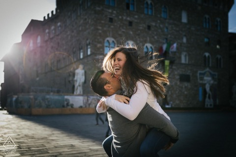 she jumped on him in the afternoon sun in Piazza della Signoria in Florence