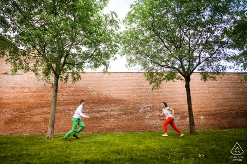A couple is running toward each other during their outdoor, park engagement portrait session in Toulouse