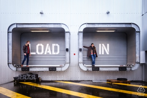 A couple posing for engagement portrait by rain & load in sign in Nantes