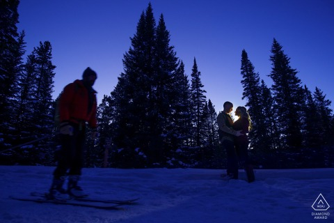 A skier skies past a couple as they embrace on Boreas Pass Road during their winter engagement photos