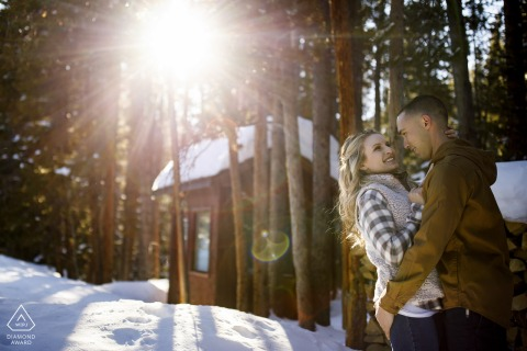 The young couple embrace as the sunlight filters through the trees at Sawmill reservoir in Breckenridge during their winter engagement session