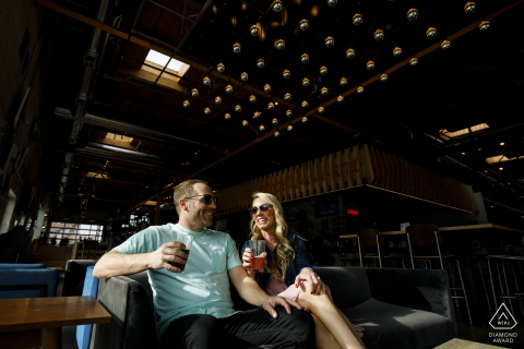 The young couple share a drink at Improper City in Denver during their engagement photos