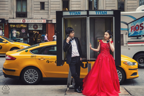 The couple were looking at each other with pay phone in their hands on a NYC street.