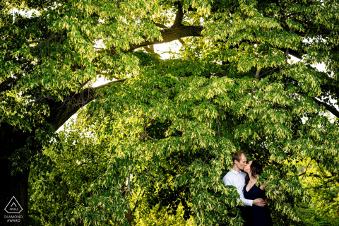engaged couple pose for portraits Hidden in the leaves of Rosice
