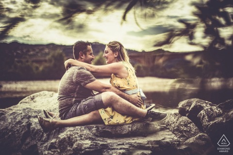 Bolano couple sitting on the rocks by the water for a portrait