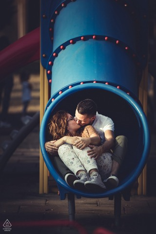 Bolano Love engagement portrait of a couple sitting on a playground slide tube