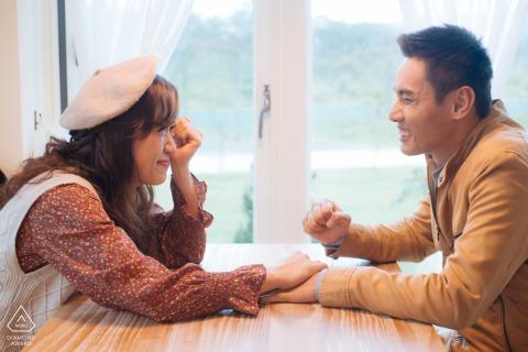 Taiwan, Hualien Indoor-Porträtsitzung vor der Hochzeit für ein junges Paar an einem Tisch