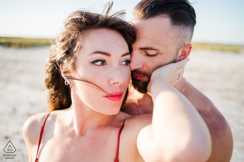 Ein verlobtes Paar umarmt sich am Strand von Camargue France für ein Porträt