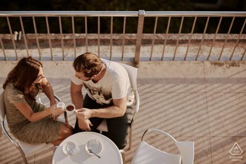 Die Braut und der Bräutigam sollen auf der Terrasse entspannt sein, während sie Kaffee und Cappuccino auf der Terrasse in Foz do Arelho, Portugal trinken