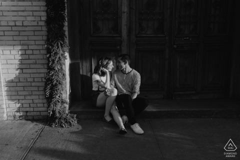 La pareja de Nueva York está sentada y hablando en los escalones bajo el sol de la tarde urbana