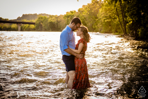 Harpers Ferry couple posing for engagement portrait In the water