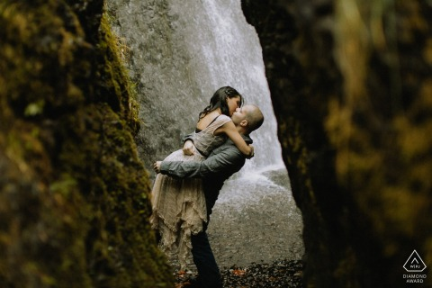 An engaged Couple kissing by a waterfall in Columbia River Gorge in Oregon for their portrait photography shoot