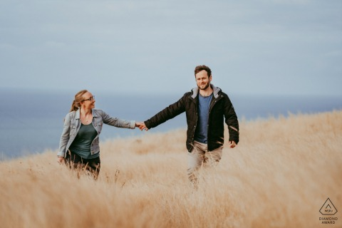 a Christchurch NZ Couple walking hand in hand in tall grass by the beach during their pre wedding photo session