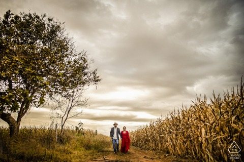 an engaged couple walks for a portrait In the middle of the road, by the burned cornfield and the approaching storm in Pirinopolis, Goias