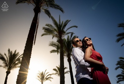 a Spain couple posing in the sunshine with sunglasses under a bright Blue Sky