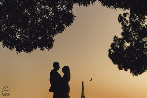 pre bride and groom with paris in the background in an engagement portrait