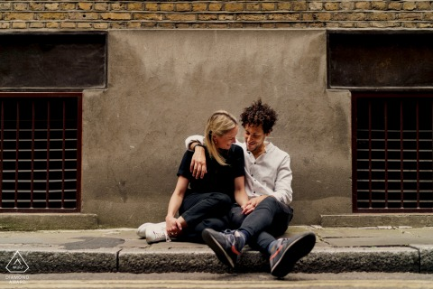 England couple sitting on the floor in London during their urban, city engagement street photoshoot