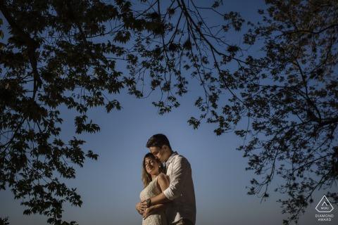 Brazil embrace by the tree that frames the engaged couple for portraits in Parque das Ruínas, Santa Teresa, Rio de Janeiro