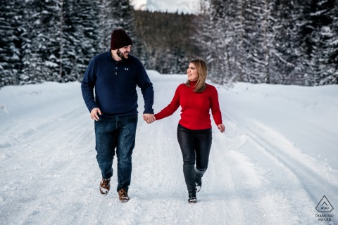 An engaged couple running together at the Banff National Park, AB, Canada