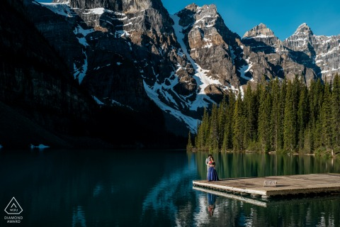 A couple Enjoying the time together during engagement portrait session on a dock at Moraine Lake, Banff National Park, AB, Canada